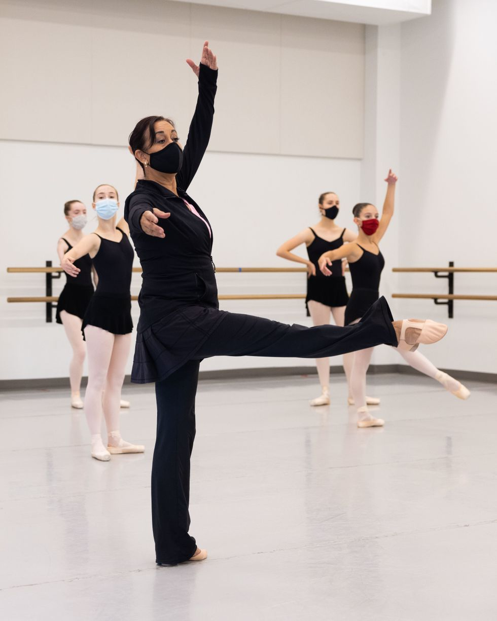 Evelyn Cisneros-Legate extends a leg croisu00e9 front at 90 degrees in center, upstage arm in fifth. Behind her, masked students in pink tights and black leotards watch or imitate. All wear face masks.