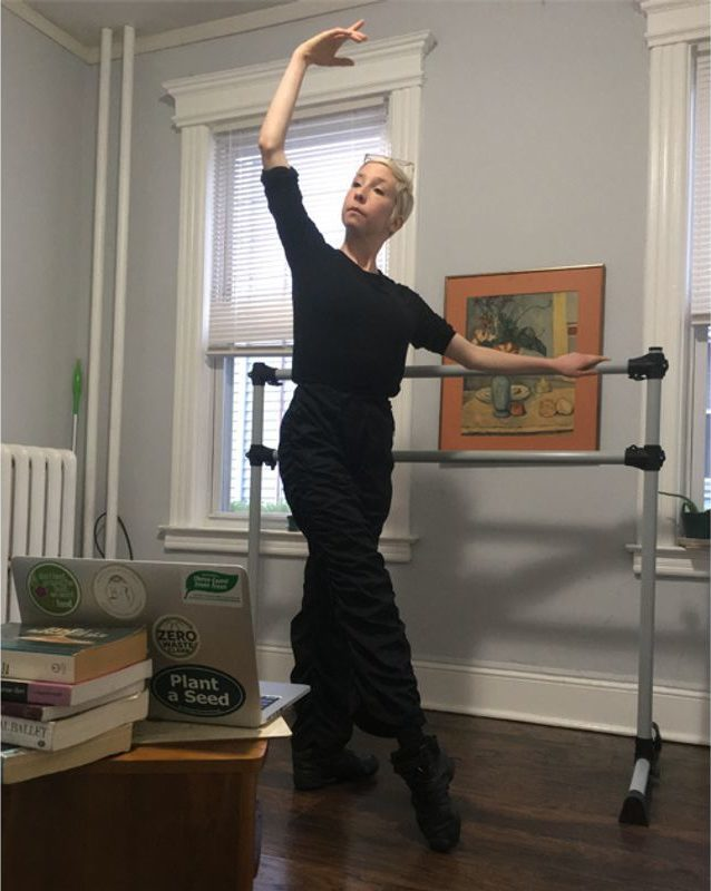 """""""Rosner, wearing all black, stands at a small barre in her home, demonstrating a tendu front to her laptop screen."""