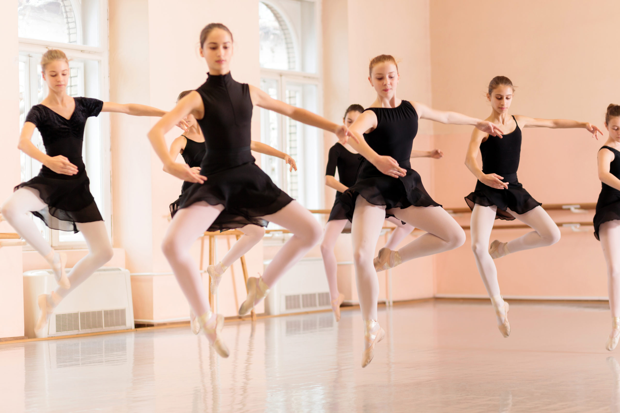 A medium group of teenage girls practice pas de chats in a large dance studio. All wear black leotards, pink tights and pink ballet slippers.