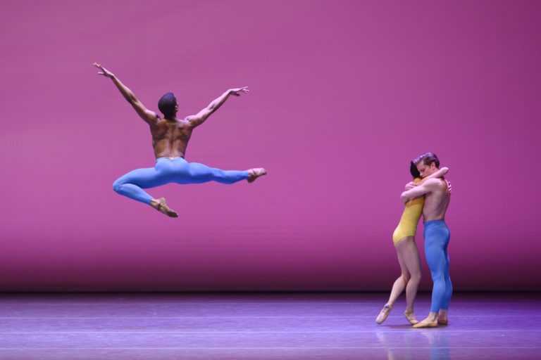 A ballet performance scene on a magenta-lit stage. A male dancer is photographed midair in a stag position from behind, his arms in a V. To his right, a man and woman embrace each other.