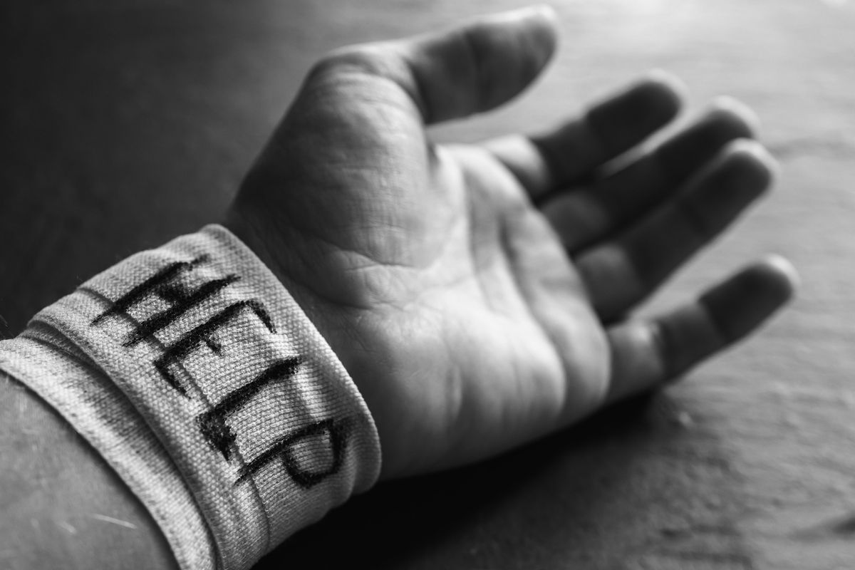 A black and white photo of a wrist, lying on a table, that has a bandage around it saying 'help'