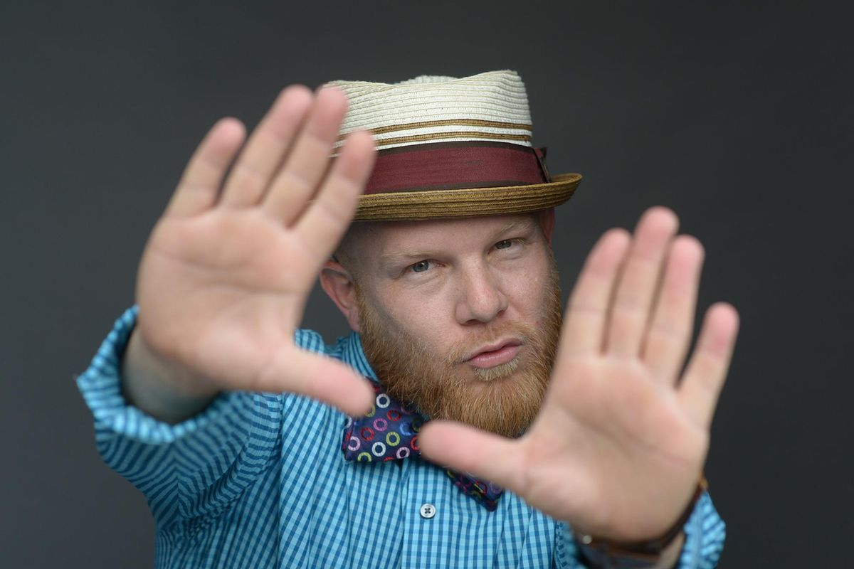 Rutledge, a middle-aged redheaded man with a beard, wears a blue checkered shirt, a colorful dotted bow tie and a hat. He reaches his hands towards the camera, framing his face