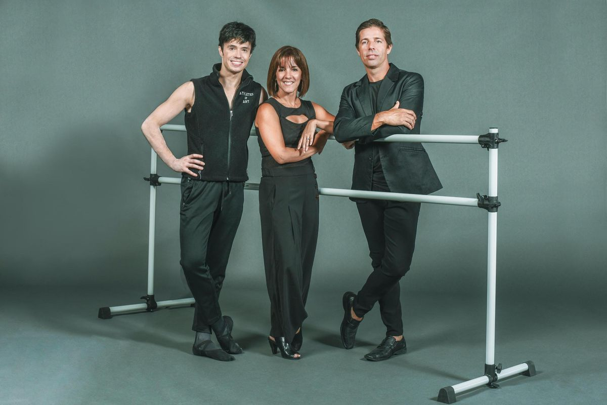 Joseph Gatti, Zoica Tovar and Andreas Estevez stand close together around a portable ballet barre in front of a gray backdrop. They are each wearing a black shirt, black pants and black shoes, and stand on one foot with their other foot crossed over, smiling towards the camera.