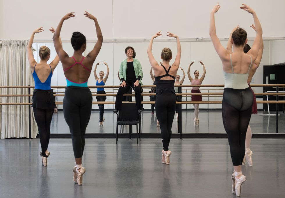 Genn sits on the barre at the front of the studio, smiling as five young women are in sous sous en pointe, with arms in fifth position