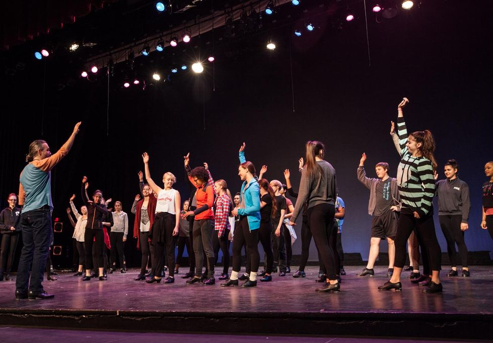Andrew Nemr, a middle-aged white man with brown-grey hair in a low ponytail, talks to a large group of teen tap dancers on a stage. He raises his hand, and some of the students do, too.