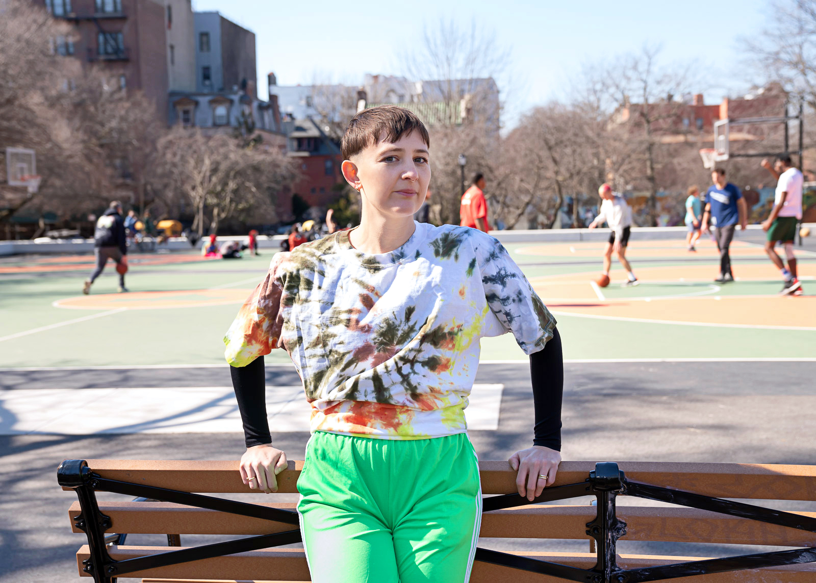 Katy Pyle, wearing a tie dye shirt and bright green shorts, leans against a park bench next to a basketball court.