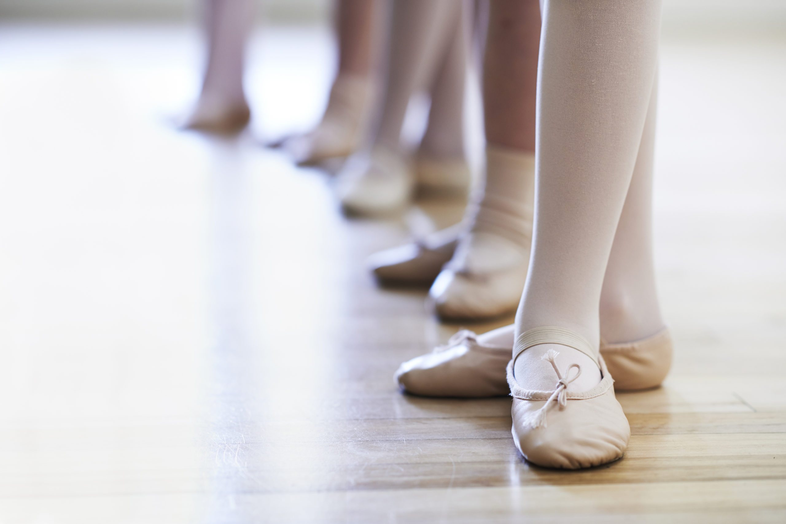 A close up of children's feet in ballet class. They wear pink tights and shoes, and are lined up in a row.