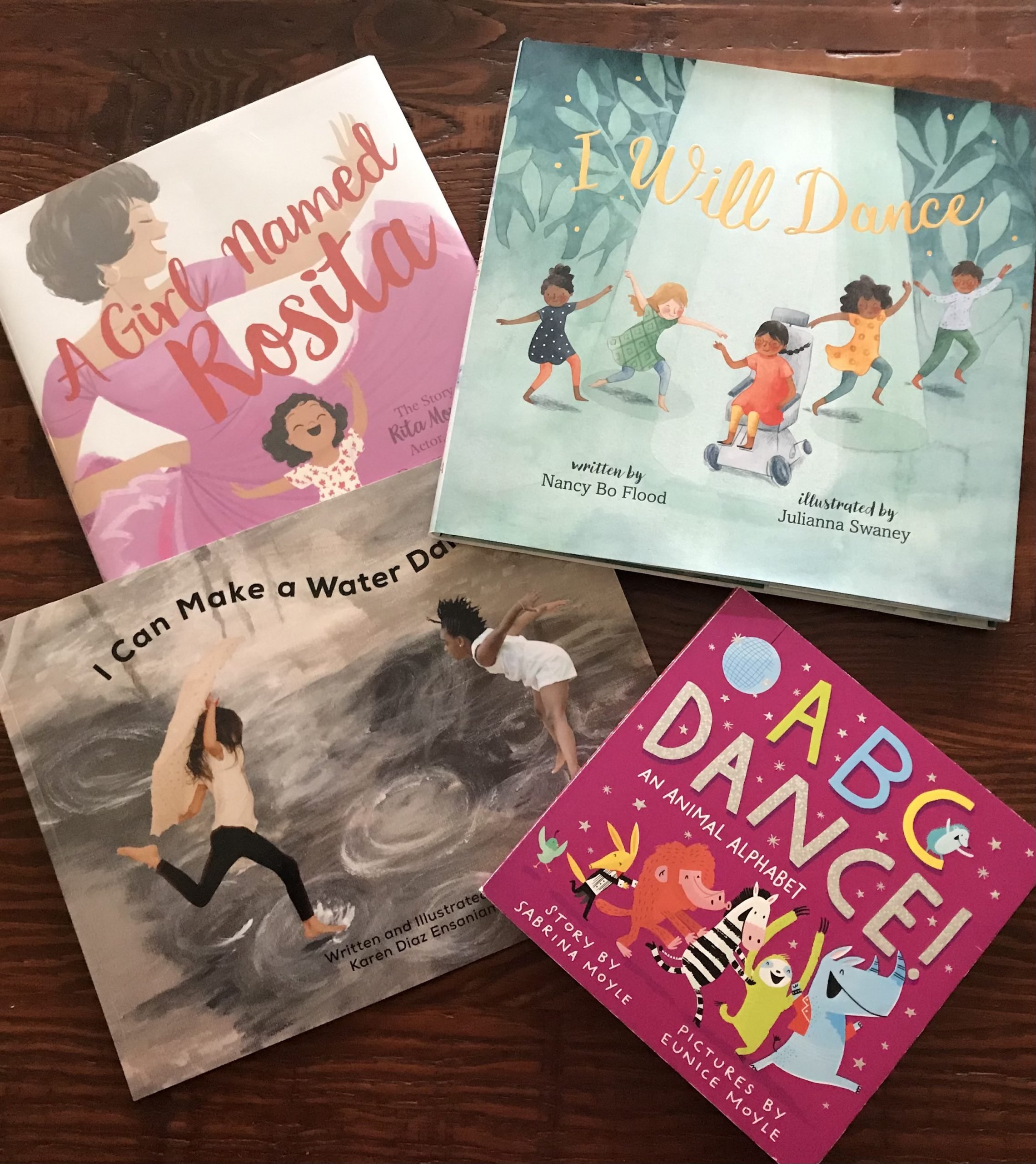 Four books—I Can Make A Water Dance, A Girl Named Rosalita, ABC Dance! and I Will Dance—splayed on a wooden table.
