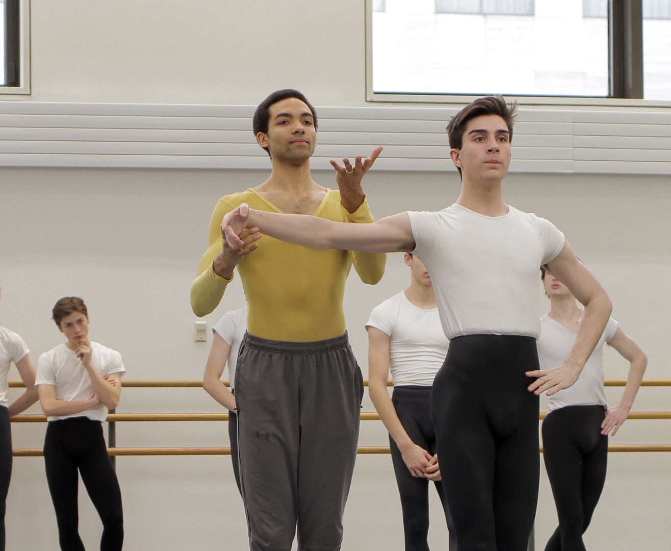 Silas Farley, a tall, slender Black man, here wearing grey sweat pants over a chartreuse biketard, gently lifts the arm of a male ballet student, making a 'lift up' gesture with his free hand.