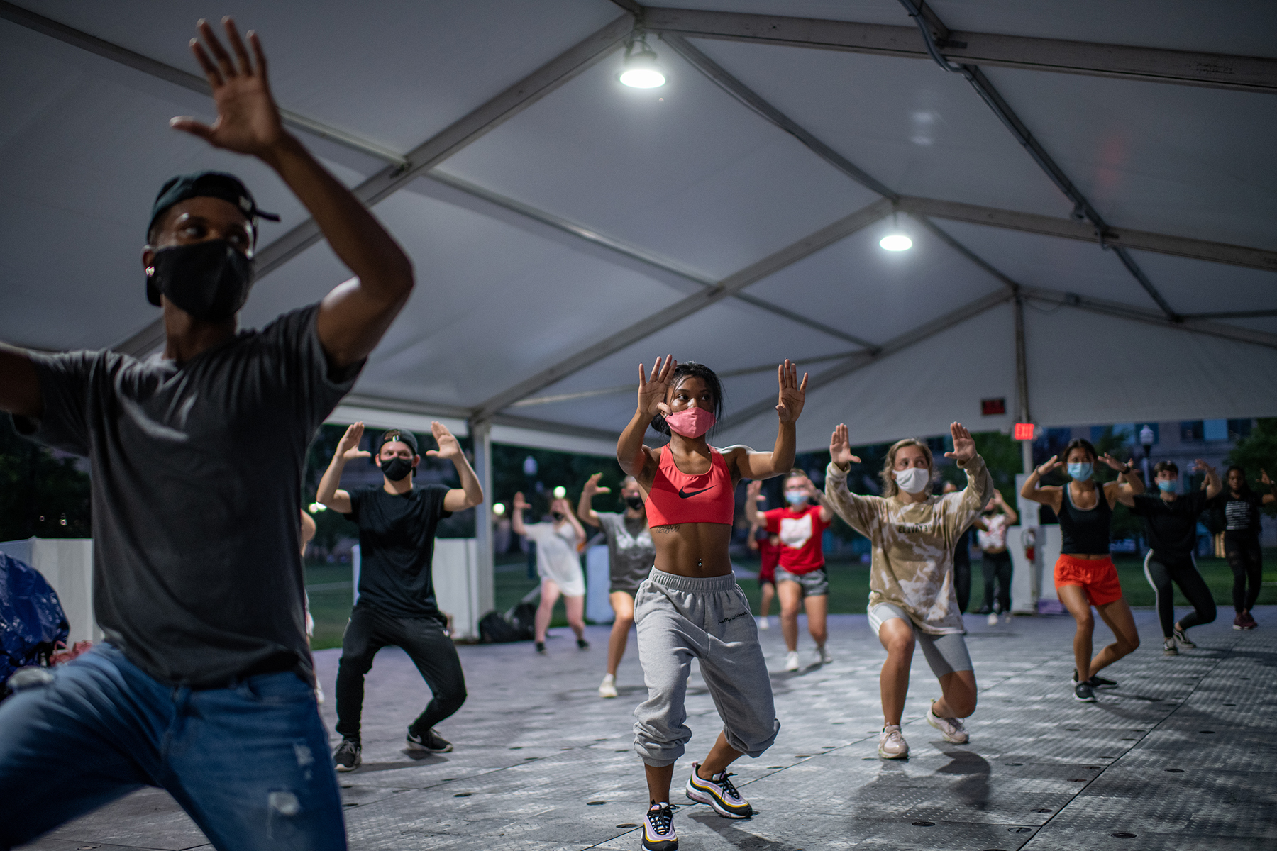 Students in sneakers and hip hop attire dance under an outdoor tent. With their heels off the ground, they turn slightly to the side with their palms up facing away from them.