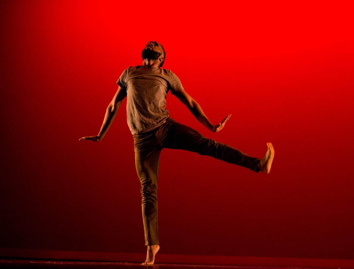A young Black man, wearing a brown tshirt and darker brown pants, leaps against a red backdrop, flexing his feet and slightly arching his back, looking up.