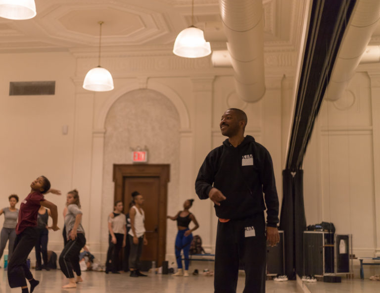 Kyle Abraham, wearing a hoodie with the A.I.M logo over the chest, smiles as he watches a group of dancers from the front of a large studio. One hand rises past his sternum as he goes to make a gesture.
