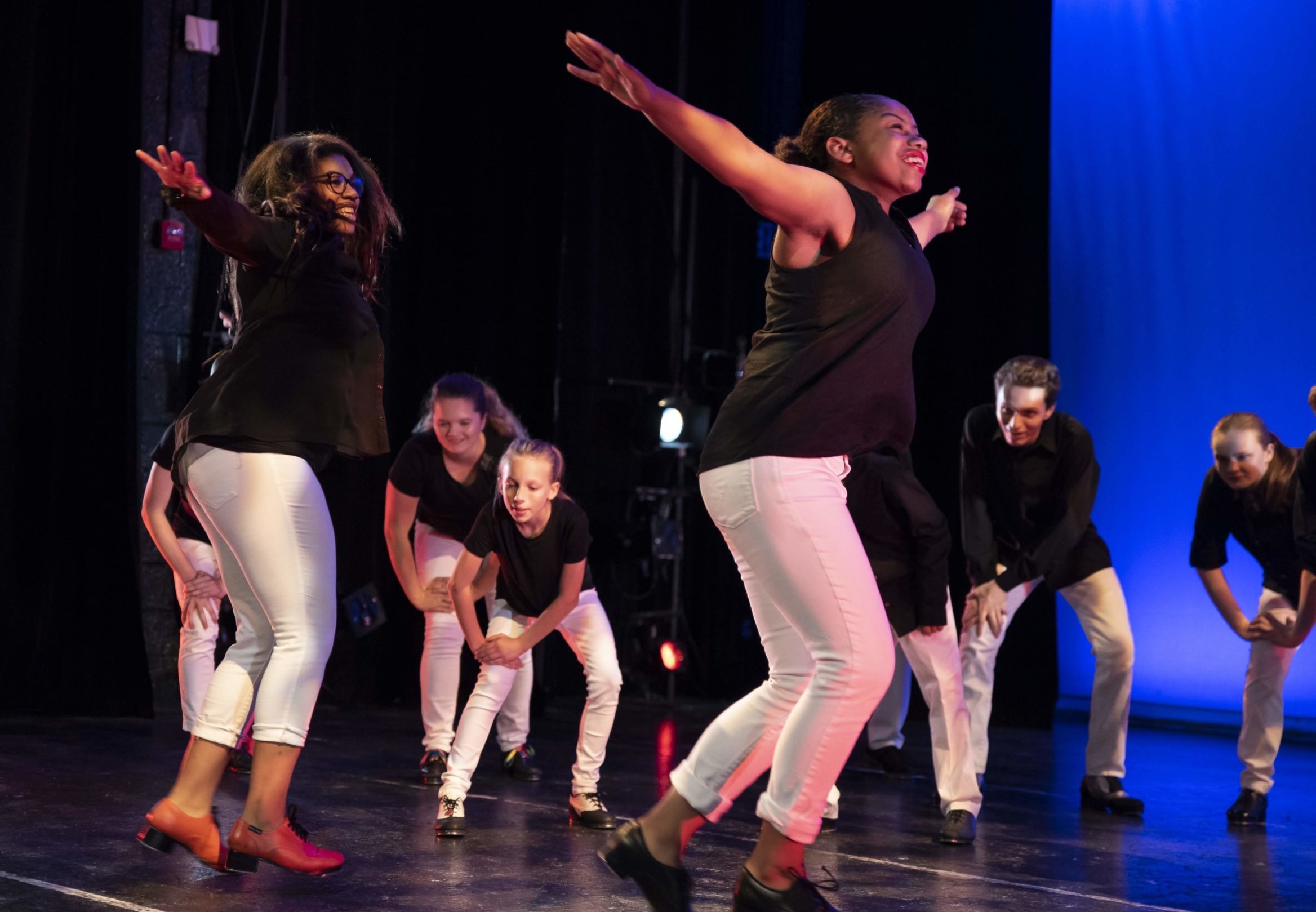 A group of teenage dancers performs onstage in white pants, black shirts and tap shoes