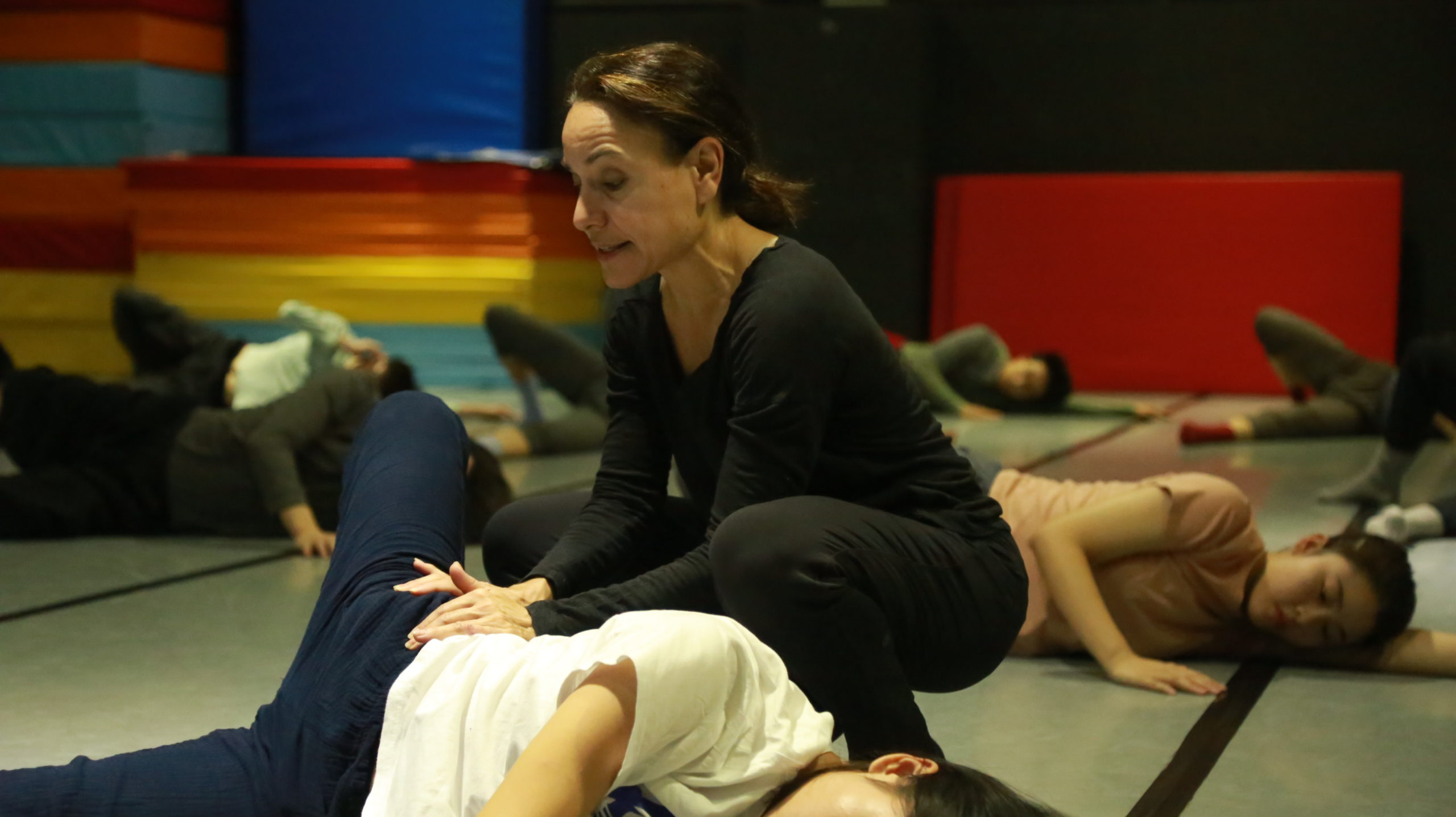 Pamela Pietro squats over a student laying on her side on the ground, adjusting her torso.
