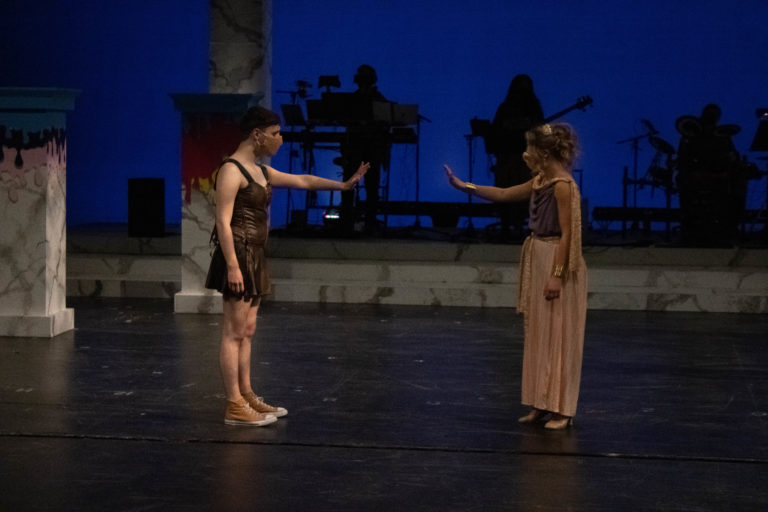 Two masked performers, a young man and a young woman, stand six feet apart onstage, reaching towards one another.