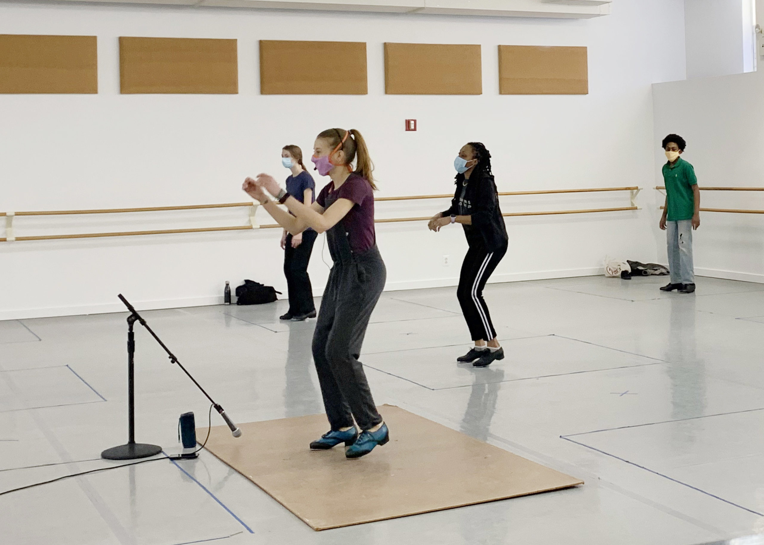 Three students of various ages take a tap class from a teacher who dancers on a tap board and has a microphone. Everyone is masked, and the students dance in boxes marked on the floor.
