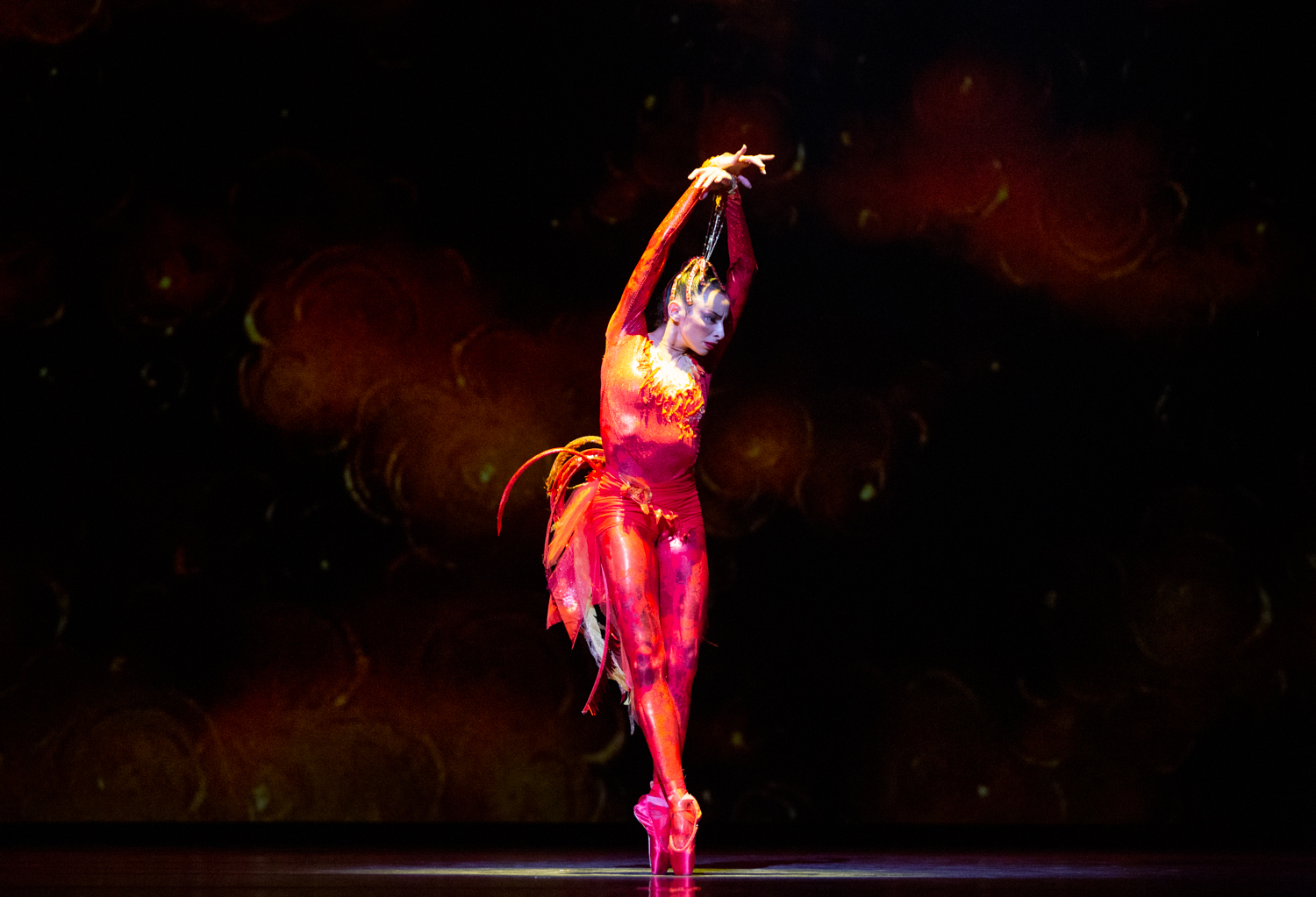 Nathalia Arja, wearing a bright red and orange bodysuit with feathers, leans slightly over, on pointe, arms raised above her head.