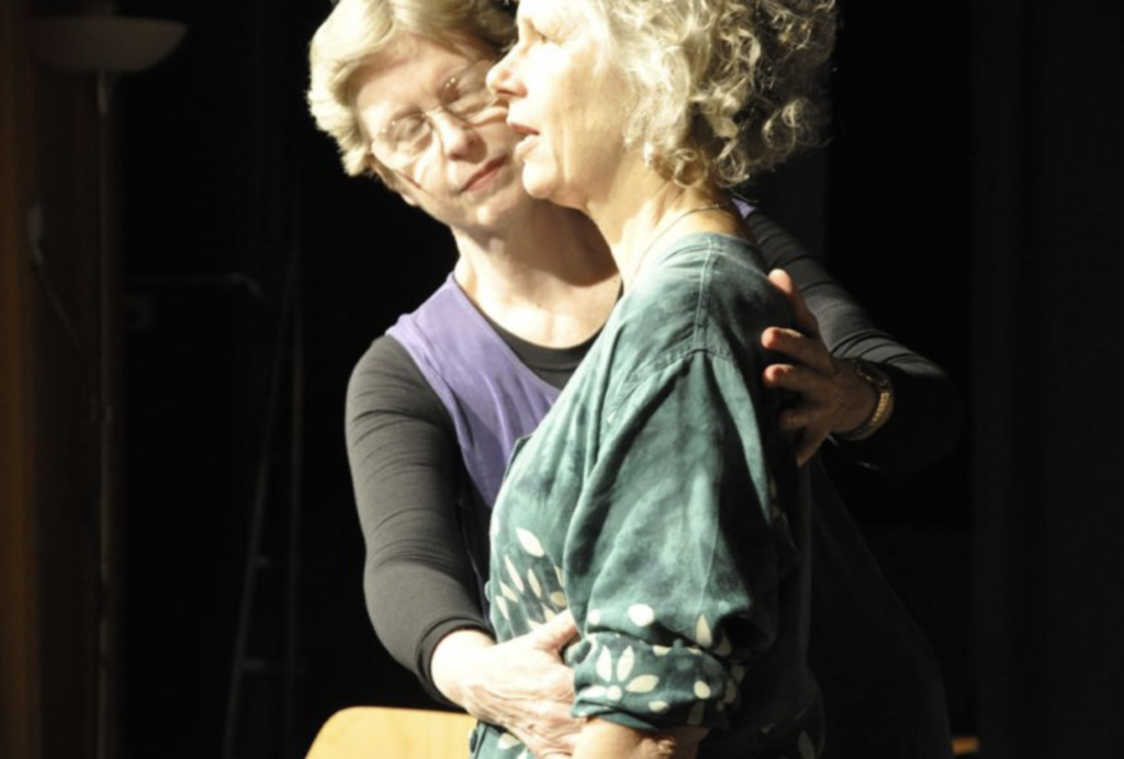 Lynn Martin places one hand on another woman's stomach, and one on her upper back.