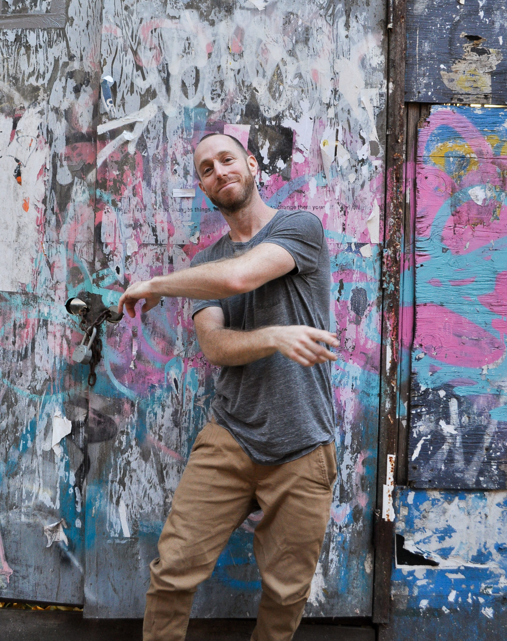 Marc Kimelman, a white man wearing a grey shirt and khaki pants, swings his arms in front of his torso, leaning slightly to the side. He is front of a colorful graffitied wall.