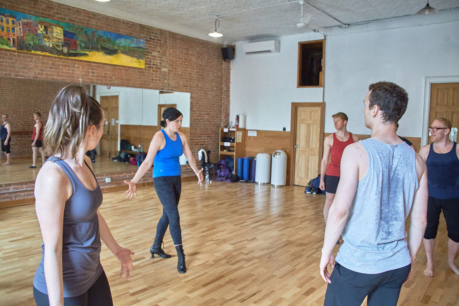 Avital Asuleen talks to a room full of dancers, who are in a semicircle around her. She is a white woman with short dark hair, wearing a blue shirt and black pants.