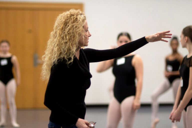 Meg Paul stands in profile with her left arm lifted to point at something off camera. Her wavy blonde hair is down around her shoulders and she wears a black long-sleeved shirt. Behind her is a student in a black leotard and pink tights.