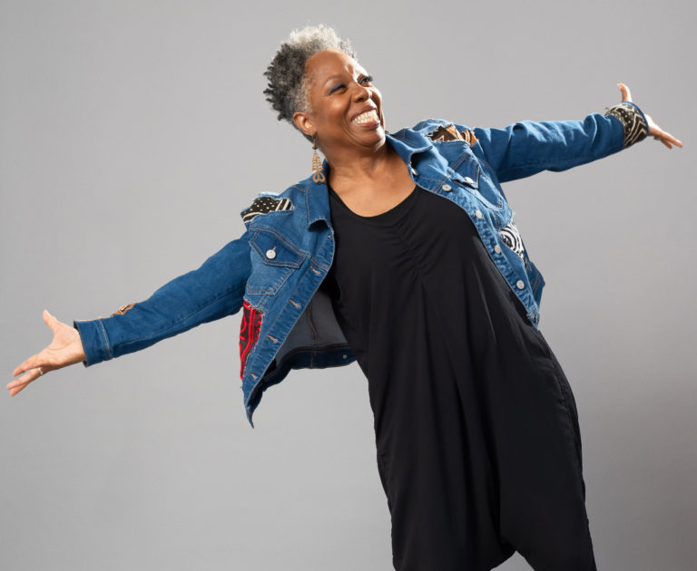Against a grey backdrop, Jawole Willa Jo Zollar smiles widely, arms thrown open to either side. She wears a denim jacket with colorful patches over a simple black dress and a pair of striking light brown geometric earrings.