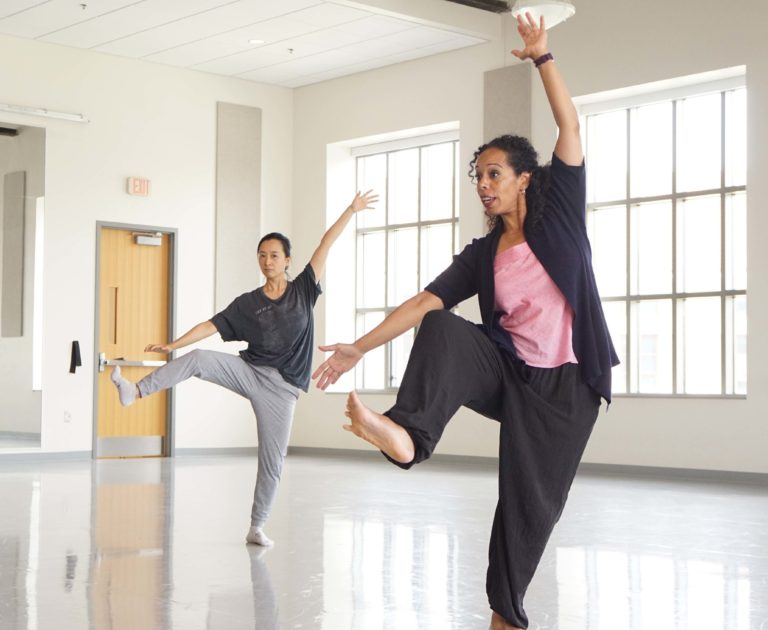 In a sunlit studio, Dr. Nyama McCarthy-Brown, dressed in loose black sweats and a jacket over a pink shirt, dark curls loosely pulled back from her face, demonstrates for a college-aged dancer. She moves through plié, her right knee pulling to her chest with a flexed foot. Her right arm is open at a downward diagonal to one side, while her left reaches with an open palm over head.